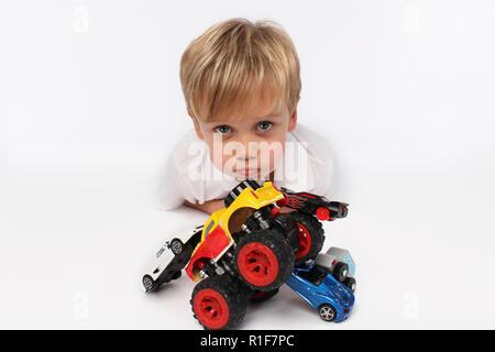 Garçon enfant mignon entouré de jouets voiture Banque D'Images