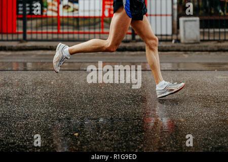 Pieds homme runner s'exécutant sur route mouillée dans la pluie Banque D'Images