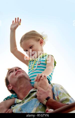 Jeune fille obtenant une épaule de voiture de son père. Banque D'Images