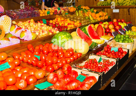 Basketsful avec récolte fraîche de poires, pommes, melons, tomates, citrons, raisins, oranges, kiwiis dans un marché de fruits. L'alimentation et les soins de concep