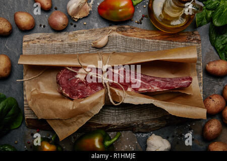 Bifteck de faux-filet cru enveloppés dans du papier sulfurisé sur planche de bois avec des herbes, épices et pommes de terre Banque D'Images