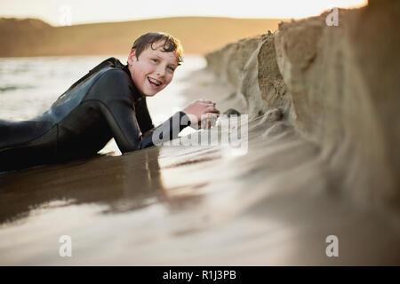 Garçon couché dans le sable à la plage dans une combinaison isothermique. Banque D'Images