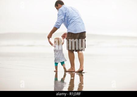 Père d'aider sa petite fille prendre ses premiers pas sur une plage. Banque D'Images