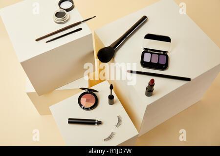 Portrait de divers accessoires de maquillage sur cubes beige
