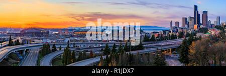 Panorama de Seattle Downtown skyline au-delà de la I-5 I-90 Freeway interchange au coucher du soleil avec une exposition longue piste de feux de circulation Dr Jose Rizal ou