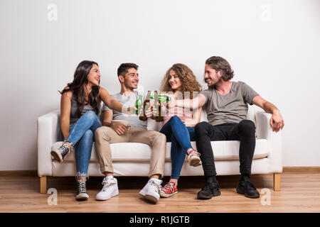 Portrait de jeune groupe d'amis assis sur un canapé dans un studio, tintement des bouteilles. Banque D'Images