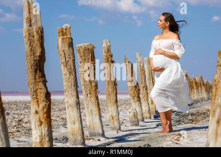 Belle jeune femme enceinte debout dans la nature sur le lac de sel. Banque D'Images