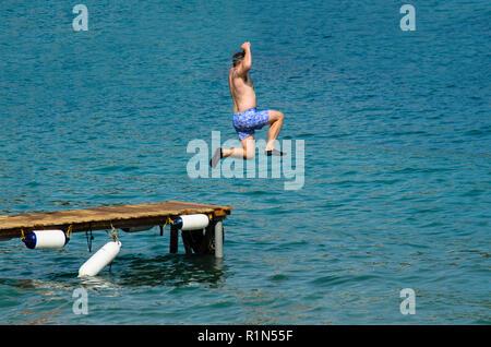 L'homme en maillot de sauter dans la mer depuis une jetée en bois, portant des chaussures en caoutchouc noir Banque D'Images