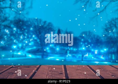 Bureau en bois avec lumière brouillée sur fond bleu. Banque D'Images