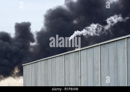 La fumée toxique d'une West Footscray Fire le 30 août 2018 peut être vu beugler derrière un entrepôt moderne contraste avec la vapeur blanche. Banque D'Images