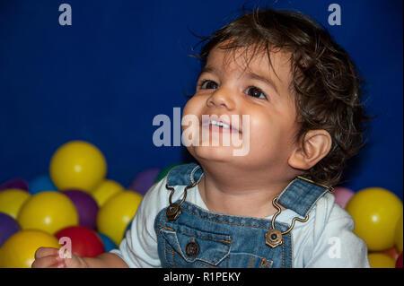 Portrait d'un enfant souriant avec de beaux yeux, assis parmi les boules colorées Banque D'Images
