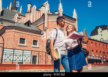 Mixed Race couple d'étudiants à pied par l'université avec des cahiers. Jeune homme arabe et blanc femme étudie à l'extérieur Banque D'Images