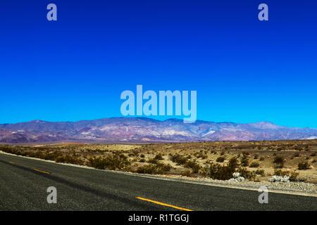 Vue panoramique vertical classique d'un interminable route droite qui traverse les paysages arides du sud-ouest américain avec la Brume de chaleur extrême sur un être Banque D'Images