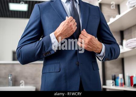Cropped shot of businessman adjusting veste de costume dans la salle de bains