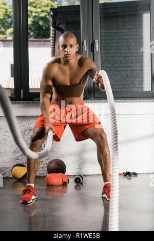 Torse nu musclé de l'athlète afro-américain travaillant avec des cordes bataille at gym Banque D'Images