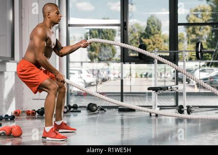 Vue latérale de l'athlète afro-américain travaillant avec des cordes bataille at gym Banque D'Images