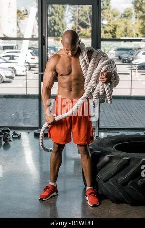 African American man musclé torse nu avec corde bataille at gym Banque D'Images