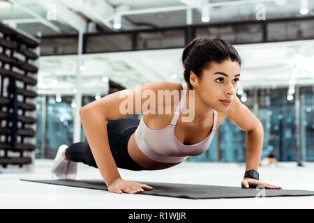 Belle jeune fille faire poussez se lève sur le tapis de fitness gym Banque D'Images
