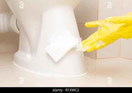 Éponge blanc sur porcelaine toilettes étant présenté avec gant de caoutchouc jaune avec de la mousse Banque D'Images