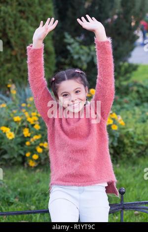 Petite fille active jeux en plein air et d'avoir du plaisir. Petite fille positive de saut. Plein air jeux interactifs. Jolie petite fille garder en forme et en bonne santé. Passer du temps dans le parc. Profiter de la nature. Banque D'Images