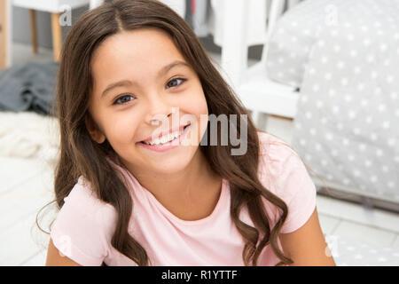 Petite fille dans la chambre. Kid smiling préparer aller au lit. Vous pourrez vous détendre le temps agréable chambre confortable. Kid fille cheveux longs pyjamas mignons se détendre avant de dormir. Le temps de sommeil ou sieste. Je lui souhaite de doux rêves. Banque D'Images