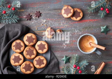 Les biscuits de Noël avec étoile chocolat avec une machine à espresso, la cannelle et le sapin décoré de brindilles. Mise à plat sur l'arrière-plan en bois rustique foncé. Banque D'Images