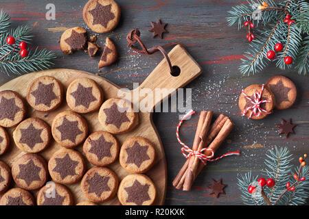 Les biscuits de Noël avec étoile chocolat avec la cannelle et le sapin décoré de brindilles. Mise à plat sur l'arrière-plan en bois rustique foncé. Banque D'Images