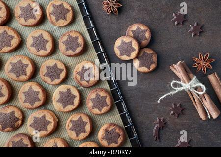 Les biscuits de Noël avec étoile de chocolat sur du papier sulfurisé sur le dessus de la grille de refroidissement avec cannelle et anis sur fond marron foncé Banque D'Images