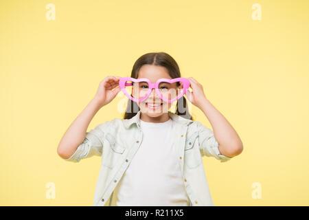 99ab8dc47715cd ... Heureux l enfant porter des lunettes en forme de coeur sur fond jaune.  Petite