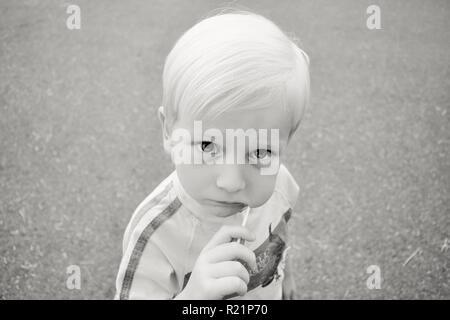 Little Boy Eating Lolly Pop en noir et blanc Banque D'Images