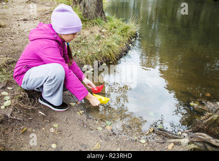 Fille en bleu chapeau, veste et pantalon gris magenta puting deux papiers de couleur bateaux dans le ruisseau outdoor le jour d'automne Banque D'Images