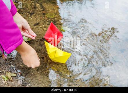 Veste fille en magenta puting deux papiers de couleur bateaux dans le ruisseau outdoor le gros plan des mains journée d'automne. Banque D'Images