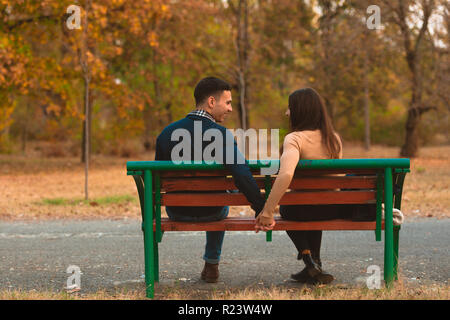 Heureux couple assis sur un banc, à des moments heureux partage de midi d'automne. Banque D'Images