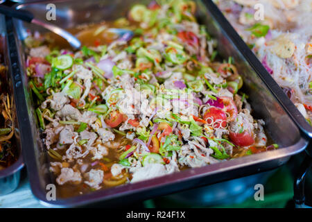 Porc épicé frais préparé salade asiatique avec légumes croquants sur le marché local à Bangkok. La cuisine thaïlandaise traditionnelle faite d'ingrédients frais. Banque D'Images