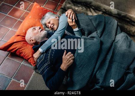 Senior couple allongé sur le sol se tenant et parler. Vieil Homme et femme dormir sur le plancher à la maison couvrant d'une couverture et de parler. Banque D'Images