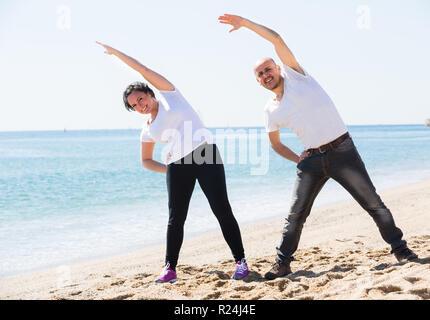 Happy smiling mature couple faisant des exercices sur la plage de sable Banque D'Images