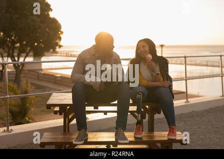 Couple having ice cream sur banc de la promenade Banque D'Images