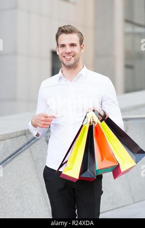 Homme Vêtements officiels portent des sacs de magasinage. Guy heureux faire bande sacs. Des affaires. C'est sur le noir vendredi. Maintenez l'homme sacs sacs papier lot après shopping in mall. Le vendredi noir vente concept.