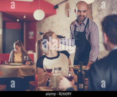 Poli garçon portant des plats commandés à smiling couple at restaurant Banque D'Images