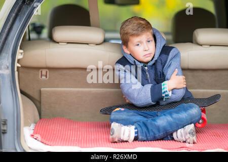 Glum petit garçon assis dans le coffre d'une voiture à hayon qui serre ses bras et grimaces à l'appareil photo Banque D'Images