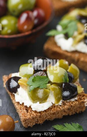 Toast de pain de seigle (canape) avec des olives noires et vertes, le fromage feta et le persil. Délicieux en-cas pour les gourmets sur une plaque en ardoise. Selective focus Banque D'Images