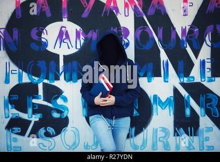 Image surréaliste comme woman student holding books et portant sur capot face invisible se pencher en arrière sur le mur de graffiti. Masque Social pour cacher son id Banque D'Images