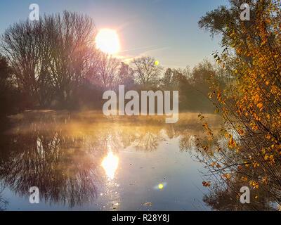 Le reflet du soleil levant sur la rivière brumeuse Banque D'Images