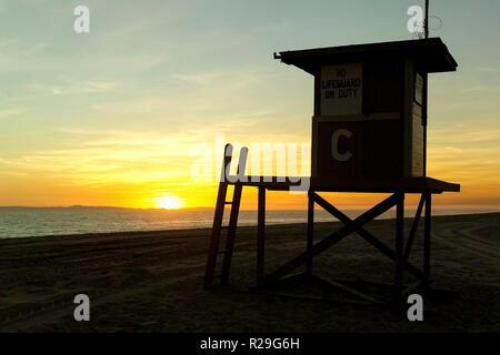 Une station de sauvetage à la fin de la journée se profile comme le coucher de soleil sur l'île de Catalina et l'océan Pacifique à Newport Beach en Californie du Sud, aux États-Unis. Banque D'Images