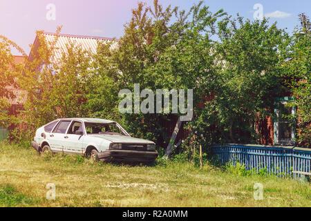 Blanc cassé vieille voiture dans la cour dans le village Banque D'Images