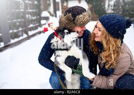 Portrait de famille de cute happy couple hugging avec leur chien malamute d'Alaska de lécher le visage de l'homme. Funny puppy wearing santa christmas bois de cerf et de lécher le visage de l'homme. Mode de vie la liberté d'animaux.