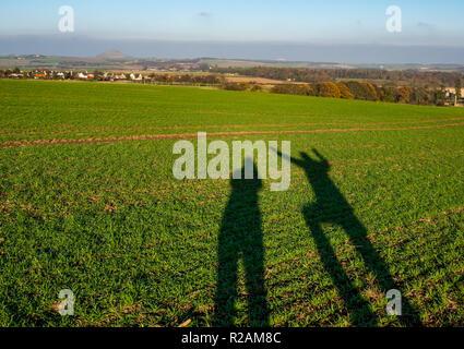 East Lothian, Ecosse, Royaume-Uni, 18 novembre 2018. Météo France: un ciel clair et du soleil sur une journée d'automne à la campagne. Le faible soleil d'hiver crée de grandes ombres d'un couple sur un champ à la recherche vers Berwick Law. L'ombre de l'homme montre les bras levés et une jambe levée comme une blague Banque D'Images