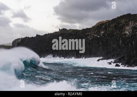 Les vagues déferlent massive contre les falaises volcaniques noires sur la côte de l'île de Terceira dans les Açores portugaises.