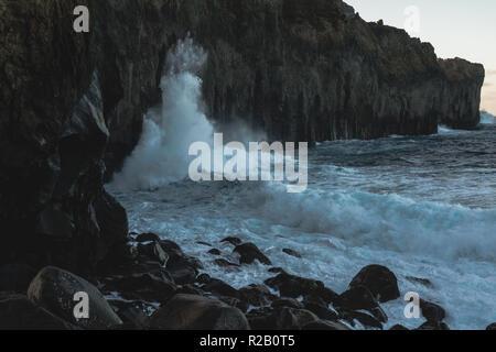 Les vagues déferlent contre les falaises volcaniques noires sur l'île de Terceira dans les Açores portugaises.