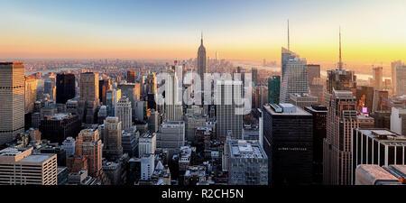 La ville de New York. Le centre-ville de Manhattan avec l'Empire State Building illuminé et gratte-ciel au coucher du soleil.